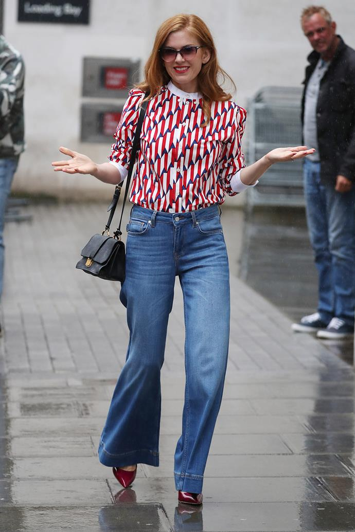 Isla Fisher channels the '70s spirit in her flared denim jeans and brightly patterned top while out in London.