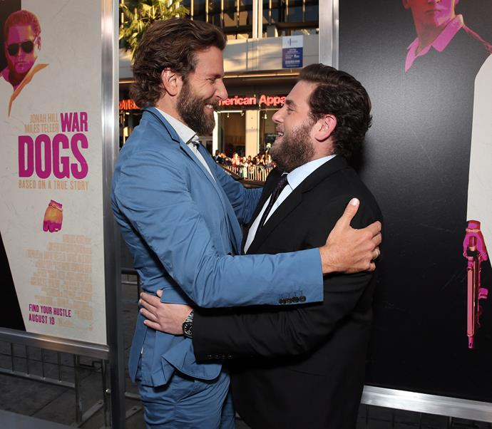 Bradley Cooper and Jonah Hill go in for a hug at the premiere of *War Dogs* in Hollywood.