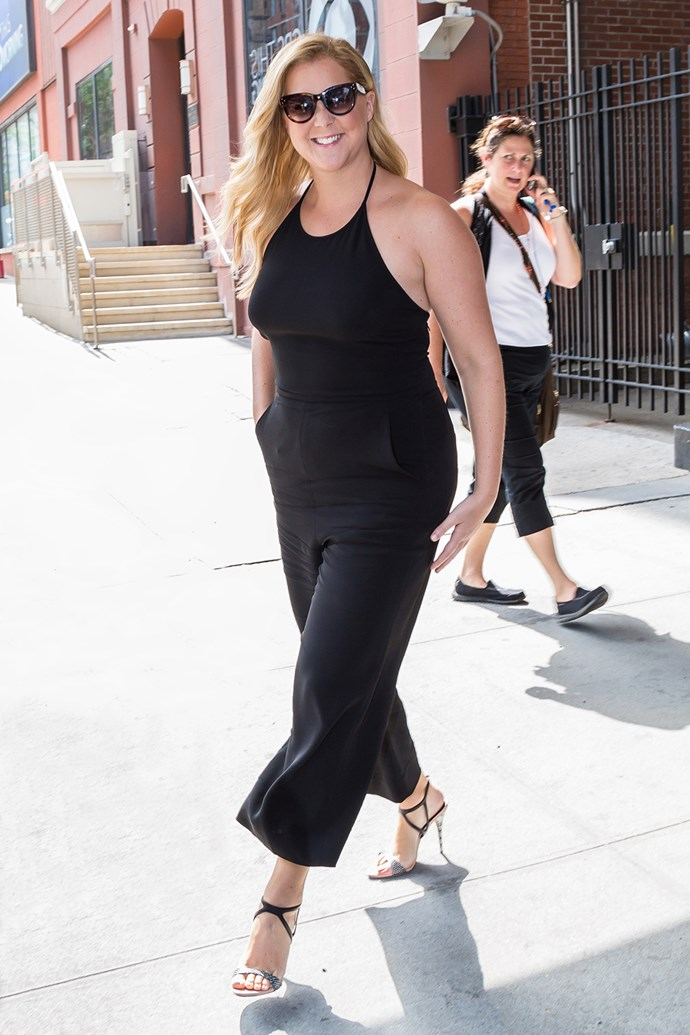 Amy Schumer flashes a grin as she prepares to film an appearance on a morning news show in New York.