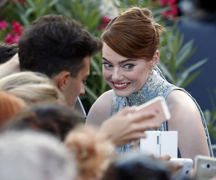 Emma Stone gets silly as she signs autographs at the Venice Film Festival premiere of her new movie *La La Land*.