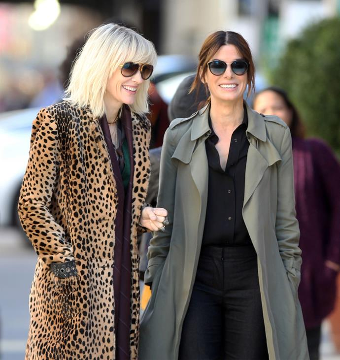 Shady ladies: The co-stars flash a smile on set of *Ocean's Eight*. Photo: Getty