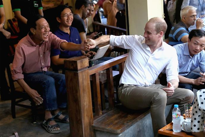 Prince William bonds with a local at a visit to a cafe. Photo: Getty