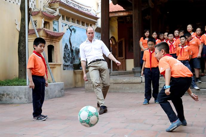 The royal takes part in a game of football with young students. Photo: Getty
