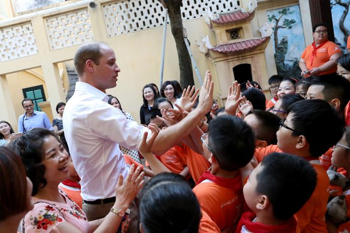 High-five! The royal says goodbye to the kids as he continues his tour of Vietnam. Photo: Getty