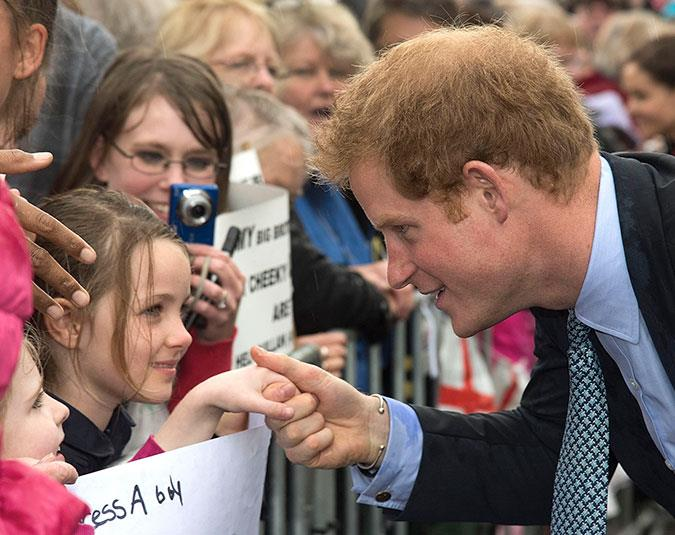 Prince Harry takes the hand of a young admirer in Whanganui.
