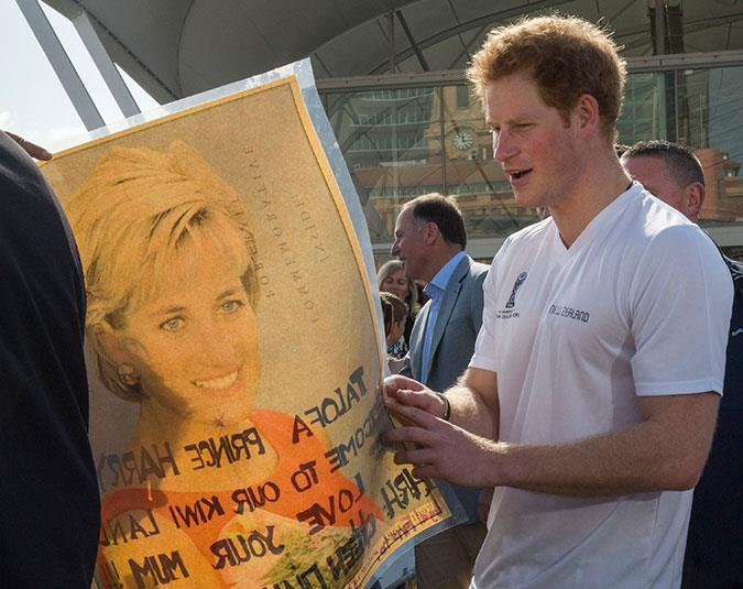Prince Harry admires a poster of his mother as he meets members of the public in Auckland