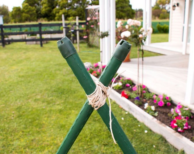 "Step 1:  Push the ends of two garden stakes into the ground in a ""V"" shape and lash them together at the top using the twine."