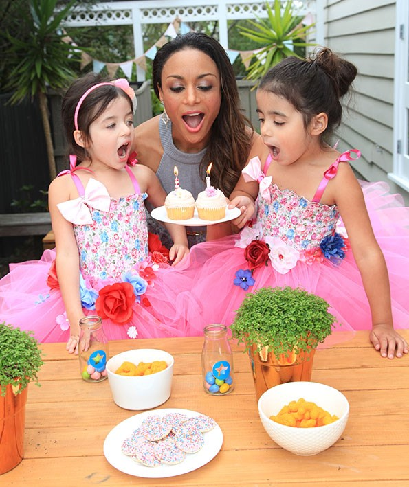 Sonia helps twin daughters Inez and Thandie blow out their birthday cake candles.