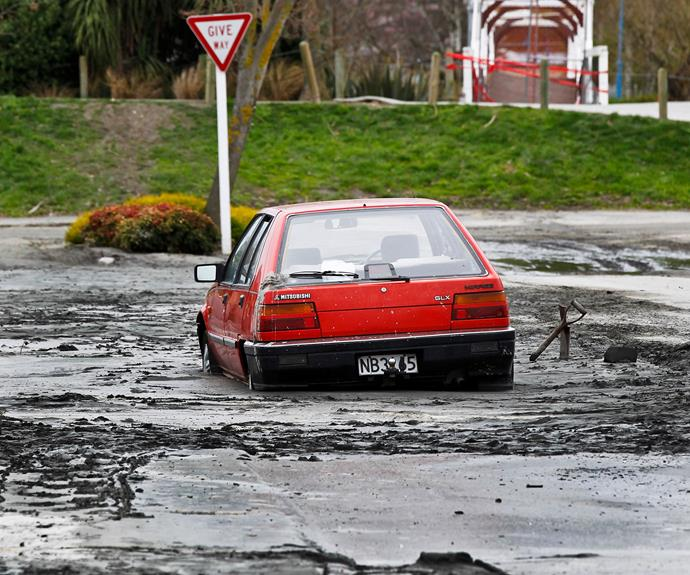 A car trapped in the street by liquefaction.
