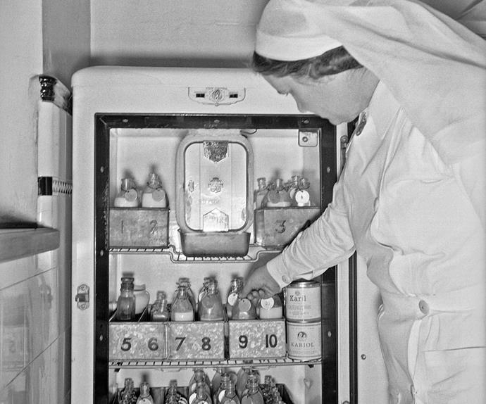 A nurse reaches inside a fridge for bottles of infant formula at the Karitane Hospital, Christchurch, 1943.
