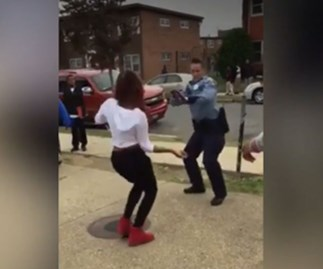 Female police officer in dance-off with teen on sidewalk