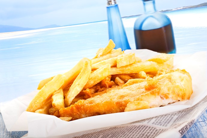Fish and chips with buttered bread and lots of tomato sauce.
