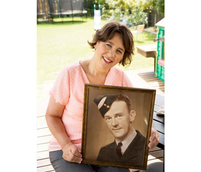 Yvonne holding a picture of her father Frank in his uniform. She knew little about his time with the Mallon crew as he didn't speak about the war.