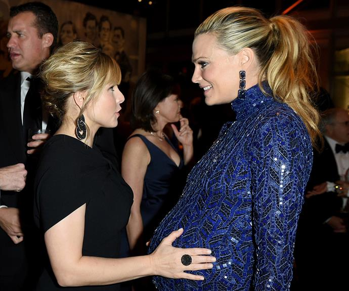 Molly Sims shows off her baby bump to Kristen Bell.