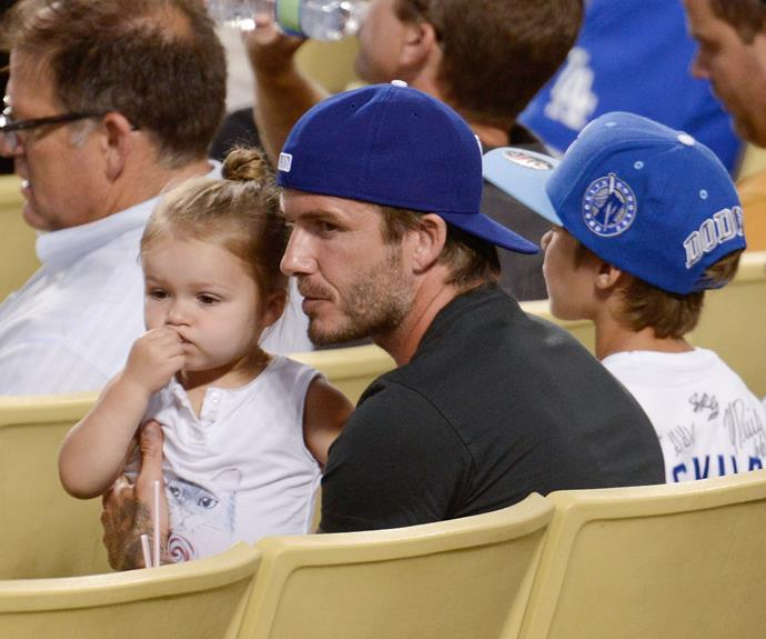 Harper looks on intently at a baseball game with her dad and brothers.
