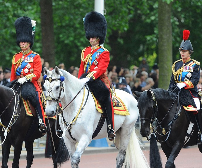Riding in on a horse is Prince Charles, Prince William and Princess Anne.