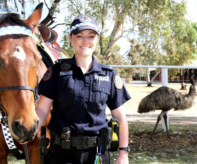 Emu hanging back as Constable Sharrah Blenkinsop poses with a horse.