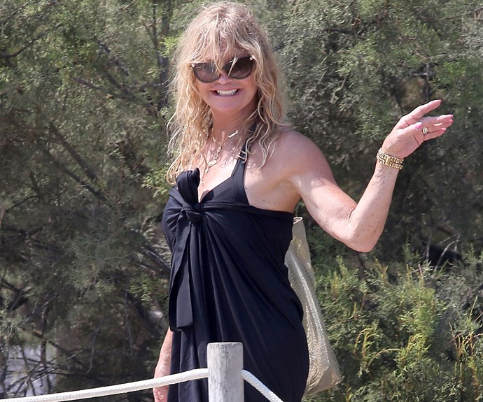 The ever-smiling Goldie Hawn radiates in a black swimsuit and matching sarong after a beach dip.