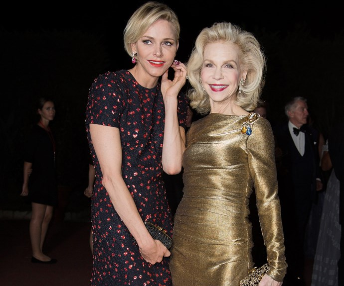 Princess Charlene smiles as she chats to American socialite Lynn Watt, who glimmered in a metallic gold floor-length gown.