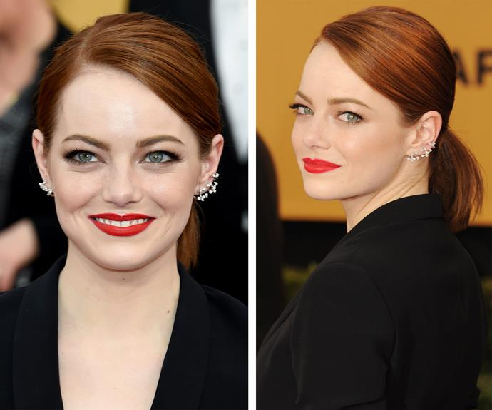 Emma Stone keeps it simple, sweeping back her vibrant locks to a side part.