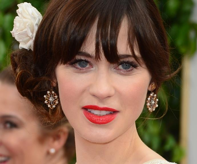 Zooey Deschanel maintains her signature quirky style with matching jeweled and real flowers.