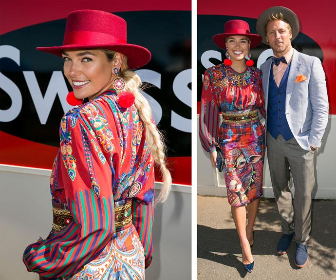 Ash Hart channels Julia Robert circa *Pretty Woman* in a red patterned silk dress, topping the outfit with a vibrant matching hat.
