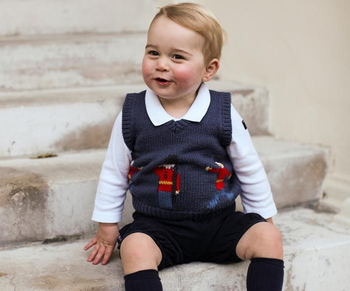 Prince George giggles as he looks at the camera.