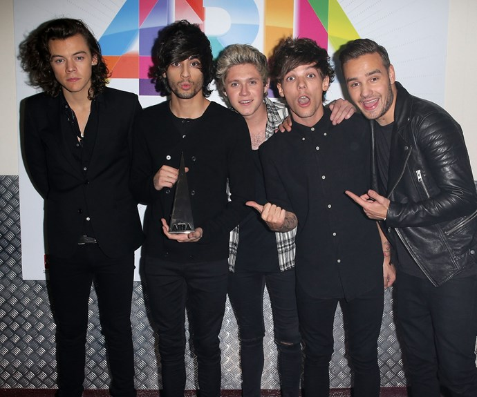 """Remember when this guy was in the band?!"" – Louis Tomlinson and Liam Payne point to now-former boy-bander Zayn Malik (or perhaps their *ARIA Award*) while posing with fellow One Direction bandmates Harry Styles and Niall Horan in 2014. The boys took home the Best International Artist Award, and performed their hit song *Steal My Girl*."
