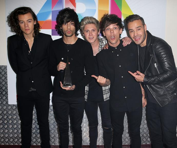 """""""Remember when this guy was in the band?!"""" – Louis Tomlinson and Liam Payne point to now-former boy-bander Zayn Malik (or perhaps their *ARIA Award*) while posing with fellow One Direction bandmates Harry Styles and Niall Horan in 2014. The boys took home the Best International Artist Award, and performed their hit song *Steal My Girl*."""