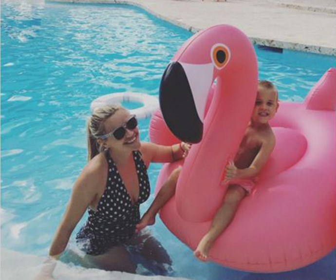 """""""Last day of vacation!"""" Reese Witherspoon knows how to do it right. The actress looked stylish in a polka-dot one-piece as her son Tennessee kicked back on an oversized flamingo."""