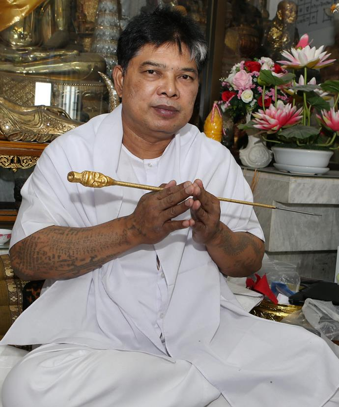 Ajarn in his Bangkok studio, holding his traditional bamboo and steel tattooing implement. *Picture: Karl Larsen/Coleman-Rayner*