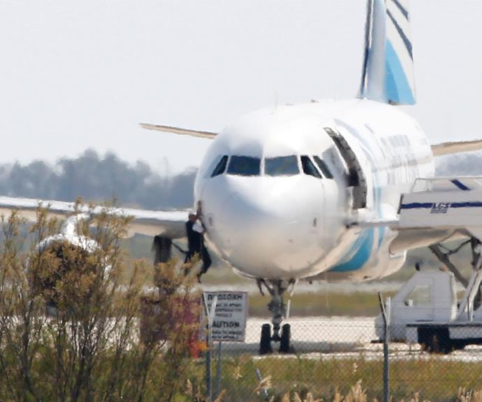 Chaos: A passenger climbs out of the cockpit window on the grounded EgyptAir plane, which was forced to make an emergency landing in Larnaca, Cyprus.