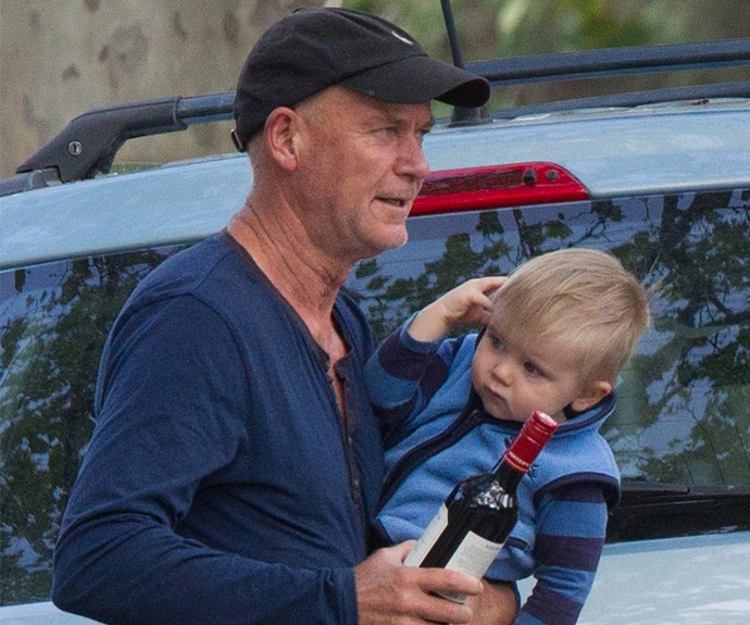 The 59-year-old actor came prepared for his dinner as he carted his bub in one hand and a bottle of red in the other.