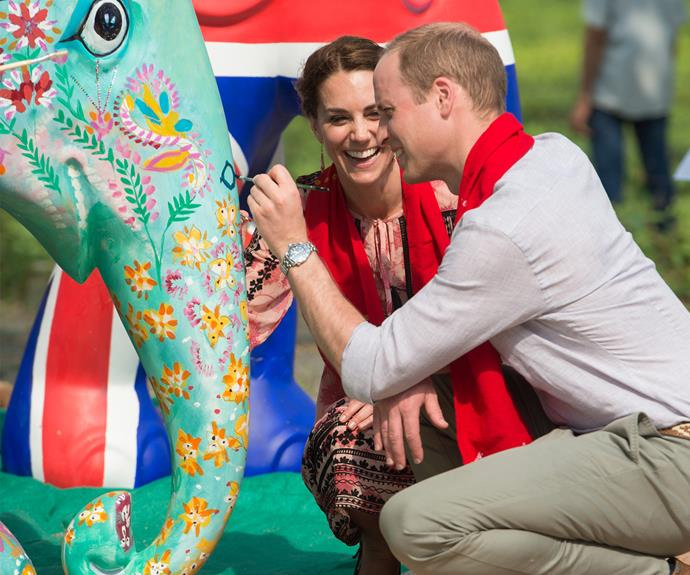 Kate can't contain her giggles as Wills attempts to do a good job.