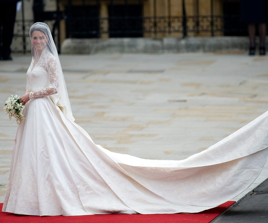**The Duchess of Cambridge, 29 April 2011** <br><br> Catherine opted for one of her favourite fashion houses Alexander McQueen to design her wedding dress for her marriage to Prince William in April 29, 2011 at Westminster Abbey. <br><br> Designed by Sarah Burton, the gown was a beautiful ivory satin, padded slightly at the hips, narrowed at the waist and inspired by the Victorian tradition of corsetry that is a particular hallmark of Alexander McQueen. <br><br> Floral motifs were incorporated into the lace and the back detail of the gown included 58 buttons of gazar and organza. <br><br> The long full skirt made of ivory and white satin gazar was designed to look like an opening flower, with soft pleats which unfolded to the floor. The outfit was finished with a short three-metre train, which was carried by her sister Pippa Middleton down the aisle.