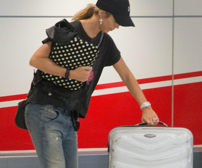 The mum-of three was spotted checking into Melbourne airport by herself, rocking a  pair of blue jeans, a black t-shirt and a black cap.