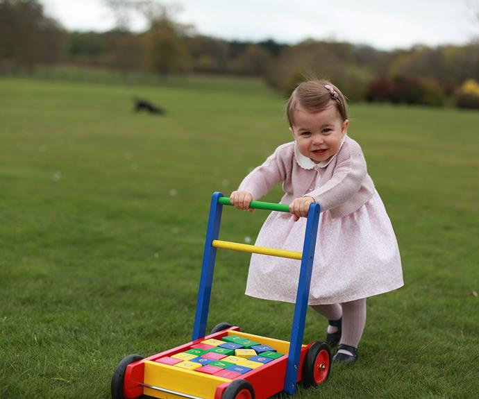 Too cute! The loving mum captured the happy moment little Charlotte pushed her toy trolley around their green gardens.
