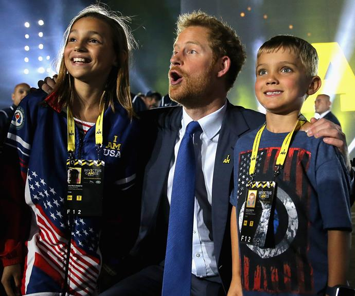 Harry hangs out with some of the Games' young helpers. Photo: Getty **Watch Prince Harry talking about inviting the Queen to the Games in the next slide**
