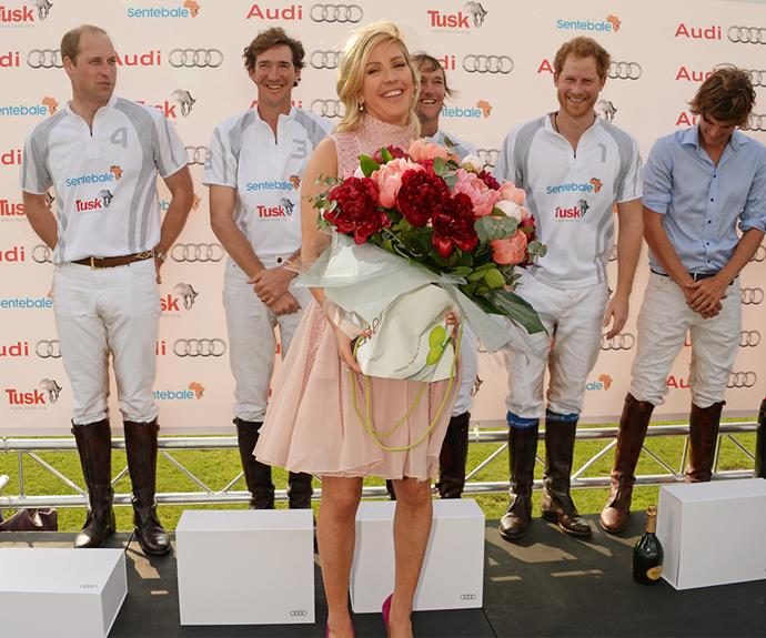 Prince Harry cheekily watches on as Ellie presents the team with a bouquet at the Audi Polo Challenge last month.