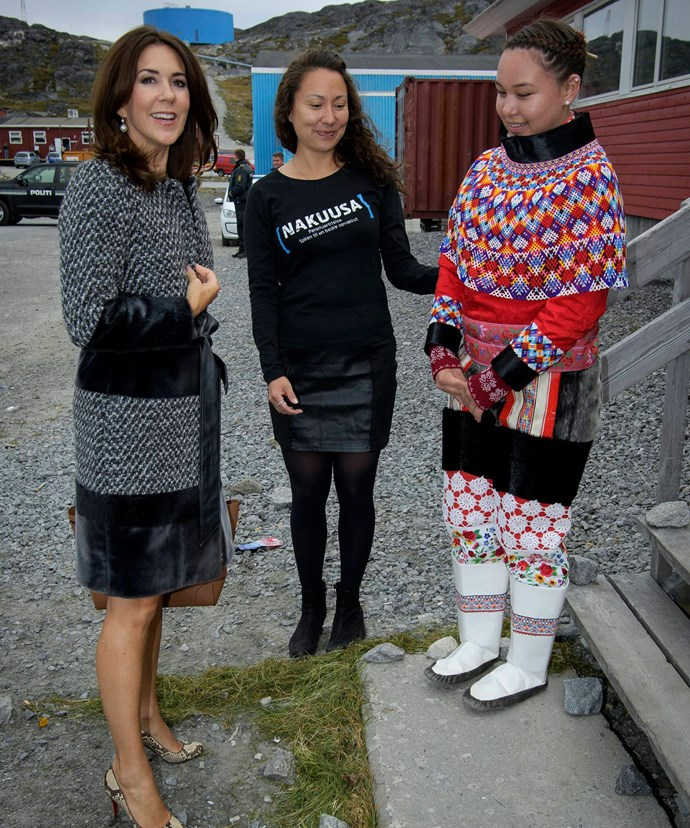 Mary chats to locals in Greenland as she wears the sealskin coat.