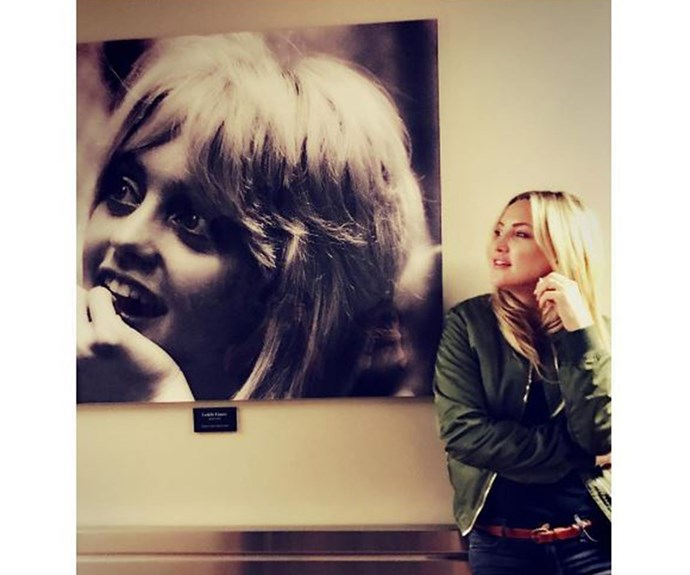 Kate Hudson strikes a pose next to a retro portrait of her mum Goldie Hawn and the pair seriously look like sisters.