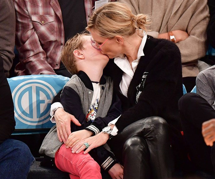 Cate gives Roman an affectionate kiss while sitting courtside.
