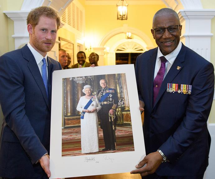 Prince Harry presents a photo of Queen Elizabeth II and Prince Philip at a reception hosted by the Governor General.