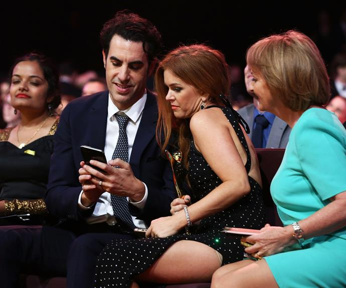 Holding her shiny new award, the Aussie stunner takes a moment to look at her husband's phone.