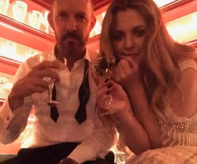 Bottoms up! A bleary-eyed Drew Barrymore enjoys the champers with a pal.