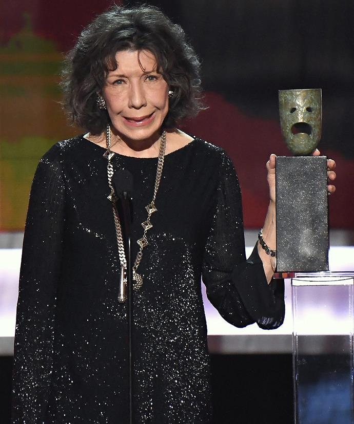 Lily Tomlin holds up her Lifetime Achievement Award.