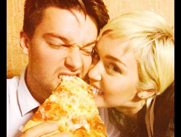 Miley, who performed Paul Simon's '50 Ways to Leave Your Lover' on the show, snuggles up to boyfriend Patrick Schwarzenegger - and a slice of pizza!