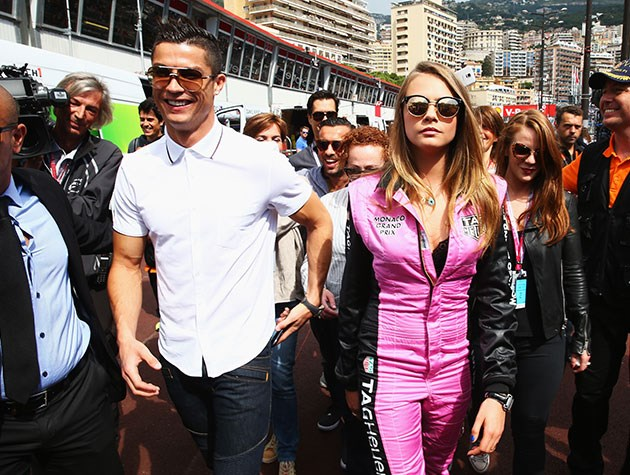 Cara Delevingne suits up next to football star Cristiano Ronaldo as they walk into the pit lane at the Monaco Grand Prix.